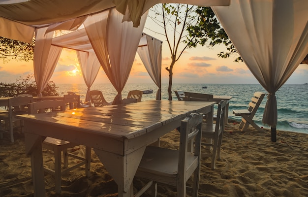 Vista al mar con mesa de diseño blanco y tela con iluminación de amanecer.