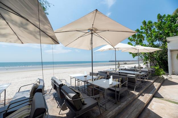 Vista al mar con mesa y sombrilla en la playa.