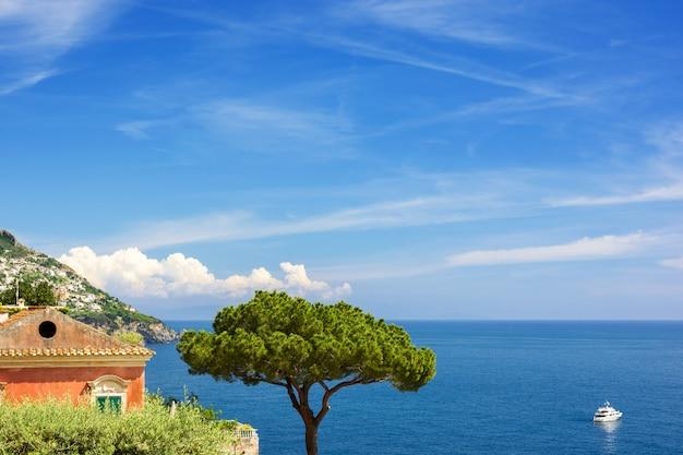 Vista al mar con pino, yate y pueblo en la costa de amalfi, ital