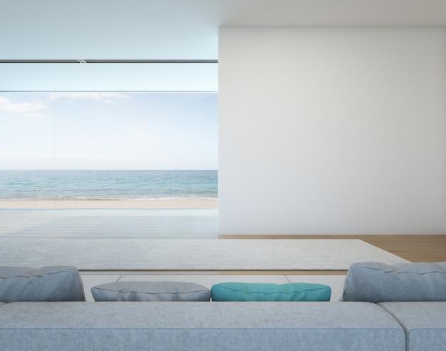 Vista al mar salón con pared blanca en casa moderna.