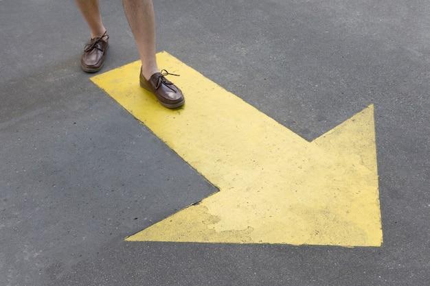 Vista alta flecha pintada de amarillo en las calles y las piernas