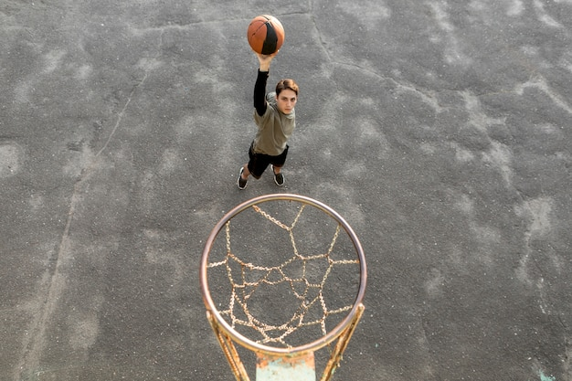 Vista alta hombre lanzando una pelota de baloncesto