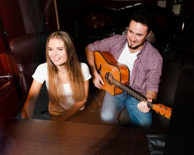 Vista alta hombre tocando la guitarra y sonrisas de mujer