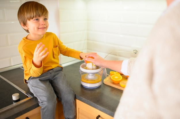 Vista alta niño haciendo jugo de naranja