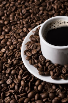 Vista alta taza de café y granos de café.