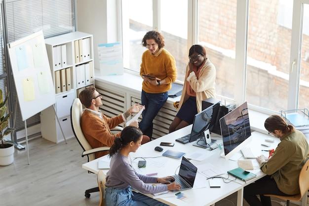 Vista de alto ángulo en el equipo de desarrollo de ti multiétnico que colabora en un proyecto empresarial mientras trabaja en el estudio de producción de software, copie el espacio