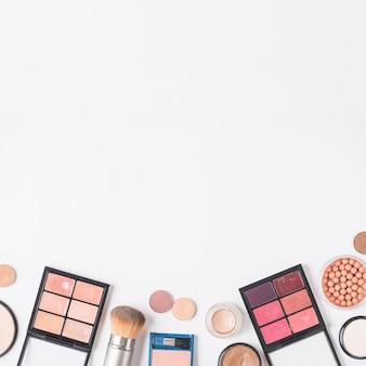 Vista de alto ángulo de kits de maquillaje en la parte inferior de fondo blanco