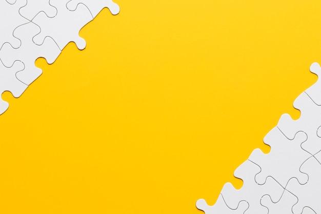 Vista de alto ángulo de pieza de rompecabezas blanco en superficie amarilla