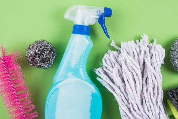 Vista de alto ángulo de los productos de limpieza en el contexto verde