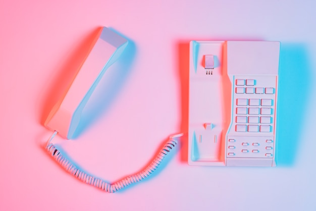 Vista de alto ángulo de teléfono fijo retro rosa con receptor