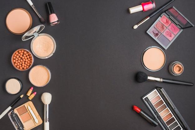 Vista de alto ángulo de varios productos de maquillaje en fondo negro