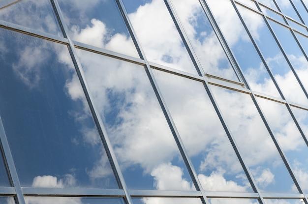 Vista angular del edificio de cristal con reflejo del cielo