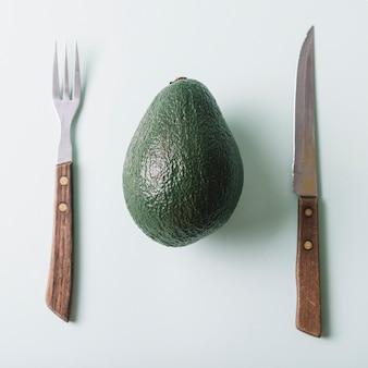 Vista de ángulo alto de aguacate fresco; cuchillo y tenedor en superficie verde