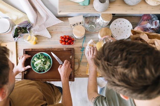 Vista de ángulo alto de amigos haciendo el desayuno en el mostrador de la cocina