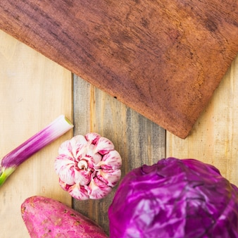 Vista de ángulo alto de la batata; ajo y repollo morado y tabla para picar sobre fondo de madera