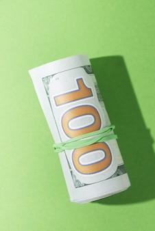Vista de ángulo alto de billetes enrollados sobre fondo verde