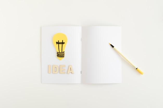 Vista de ángulo alto de la bombilla de luz amarilla con texto de idea en la tarjeta blanca