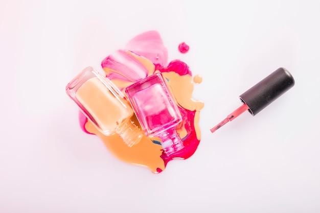 Vista de ángulo alto de botellas con esmalte de uñas derramado sobre fondo rosa