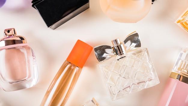 Vista de ángulo alto de botellas de perfume sobre fondo blanco
