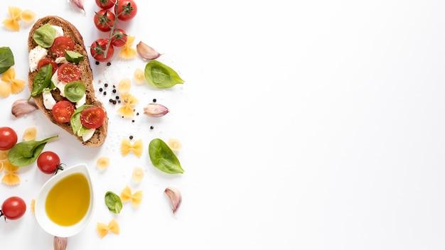 Vista de ángulo alto de bruschetta con pasta cruda farfalle; diente de ajo; tomate; petróleo; hoja de albahaca contra aislados sobre fondo blanco