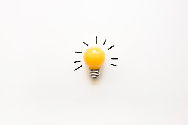 Vista de ángulo alto de bulbo eléctrico amarillo sobre fondo blanco