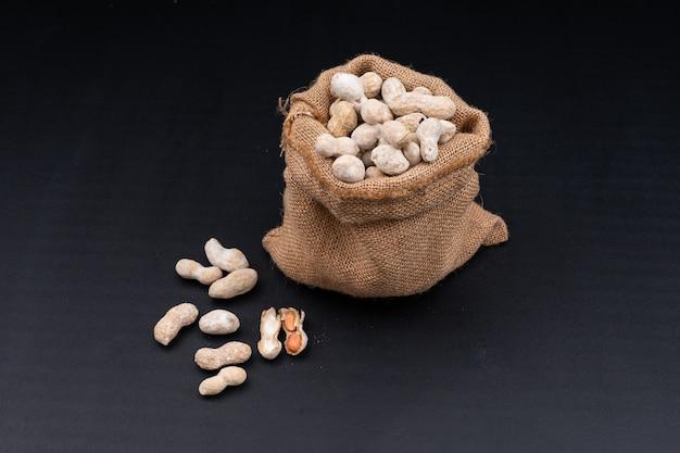 Vista de ángulo alto cacahuetes crudos en saco en negro horizontal