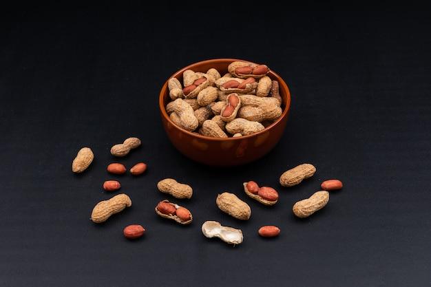 Vista de ángulo alto cacahuetes crudos en un tazón en horizontal oscuro