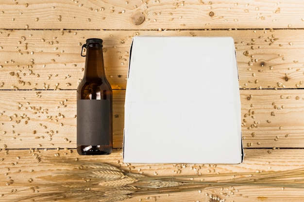 Vista de ángulo alto de la caja de cartón; botella de cerveza y espigas de trigo en tablón de madera