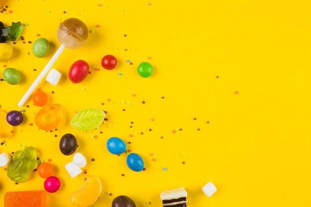Vista de ángulo alto de caramelos de colores y piruletas sobre fondo amarillo