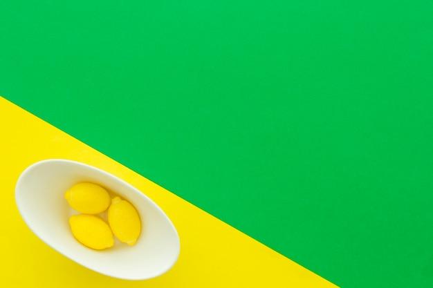 Vista de ángulo alto de caramelos de limón en un tazón sobre fondo multicolor