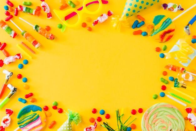 Vista de ángulo alto de caramelos; piruletas; velas; fiesta en y soplador en superficie amarilla