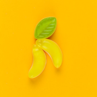 Vista de ángulo alto de caramelos de plátano sobre fondo amarillo