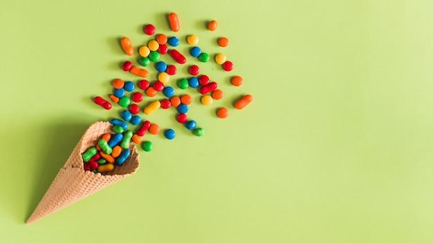 Vista de ángulo alto de caramelos que se derraman desde el cono de helado waffle sobre fondo verde