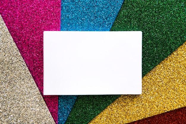Vista de ángulo alto de cartulina blanca sobre alfombra multicolor