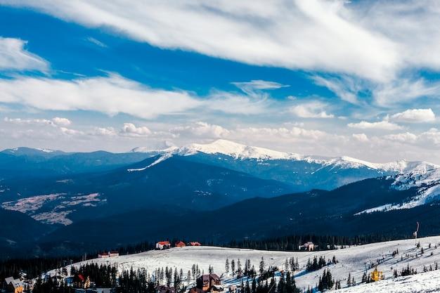 Vista de ángulo alto de casas sobre el paisaje de montaña nevada