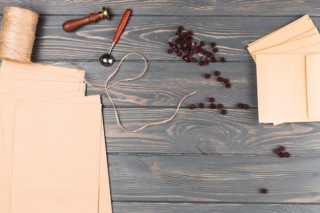 Vista de ángulo alto de cera marrón; carrete de hilo; sello de lacre; en blanco envolver tarjeta en mesa de madera