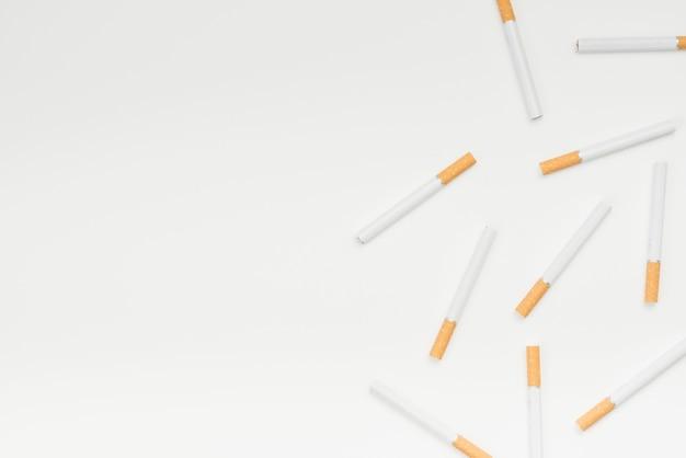 Vista de ángulo alto de cigarrillos contra la superficie blanca