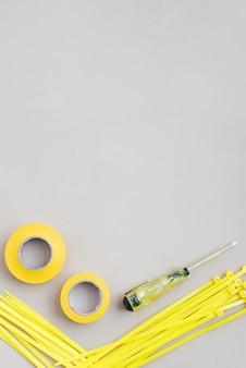 Vista de ángulo alto de cinta amarilla y cable de nylon con destornilladores eléctricos.