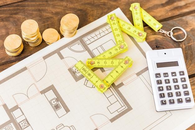 Vista de ángulo alto de cinta métrica, calculadora, monedas apiladas y blueprint
