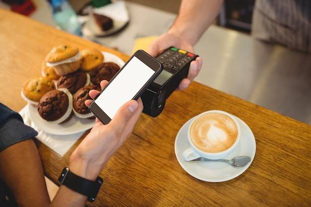 Vista de ángulo alto de cliente y barista con tecnologías en cafe