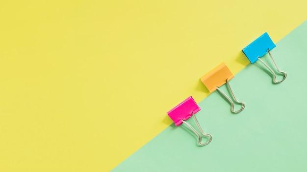 Vista de ángulo alto de clips de bulldog multicolores sobre fondo dual