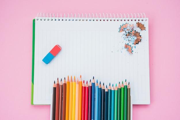 Vista de ángulo alto de los colores de lápiz con borrador y lápiz afeitado en un cuaderno espiral