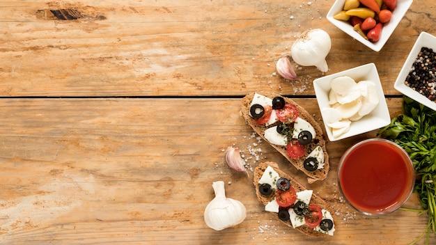 Vista de ángulo alto de comida italiana con ingredientes sobre mesa de madera