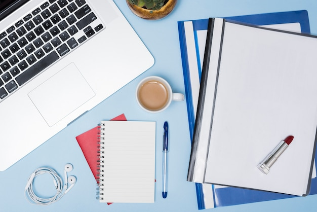 Vista de ángulo alto de la computadora portátil; carpetas; taza de café; auricular; bloc de notas espiral y pluma contra fondo azul