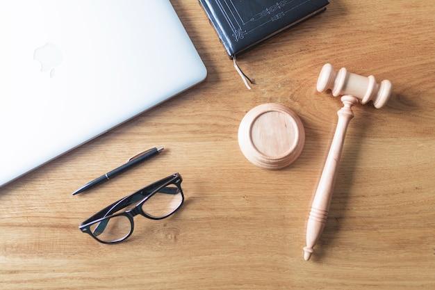 Vista de ángulo alto de la computadora portátil; gafas; martillo y pluma sobre fondo de madera en el escritorio de madera