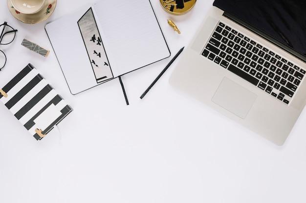 Vista de ángulo alto de la computadora portátil y papelería en mesa blanca