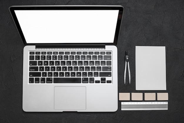 Vista de ángulo alto de la computadora portátil y papelería sobre fondo negro