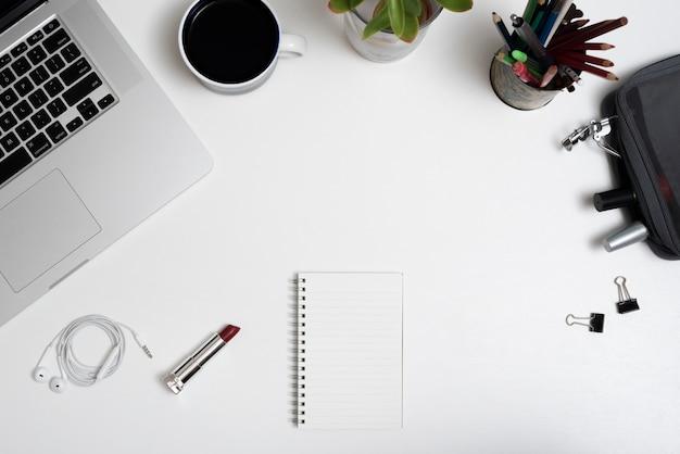 Vista de ángulo alto de la computadora portátil; taza de café; bolsa de maquillaje y lápices en escritorio de oficina