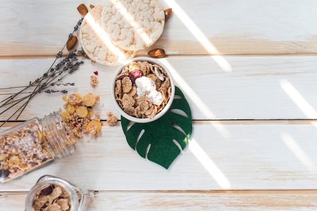 Vista de ángulo alto de copos de maíz en un tazón cerca de granola derramada y galletas de arroz en superficie de madera
