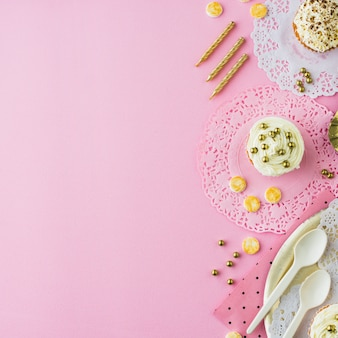 Vista de ángulo alto de cupcakes; dulces y velas sobre fondo rosa